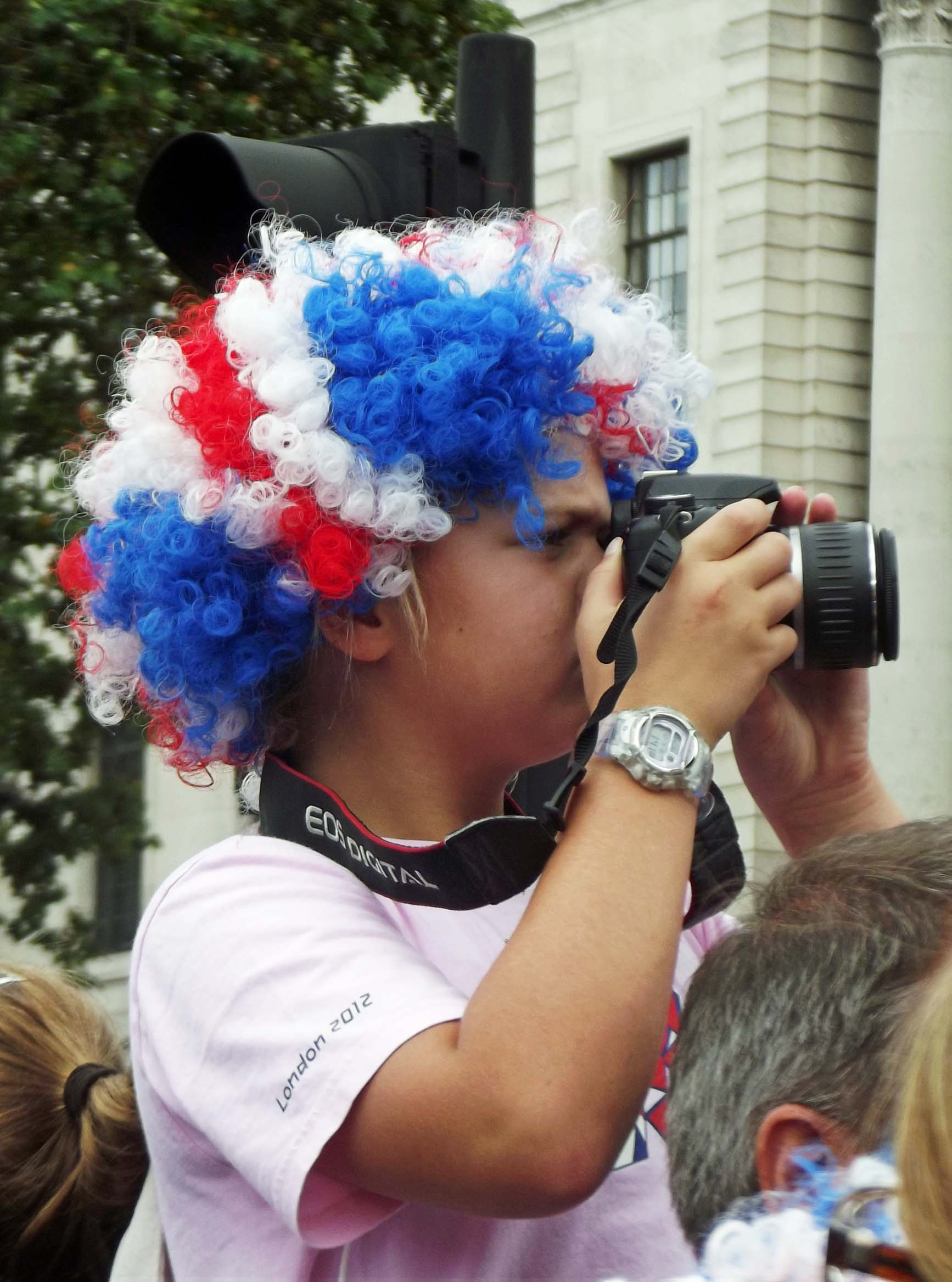 Young child with red, blue and white wig, and camera