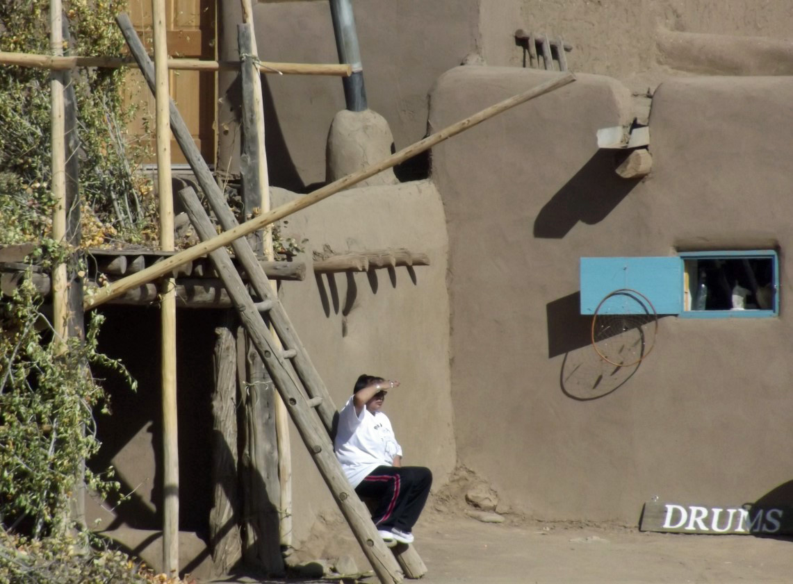 Man on ladder outside shop advertising drums
