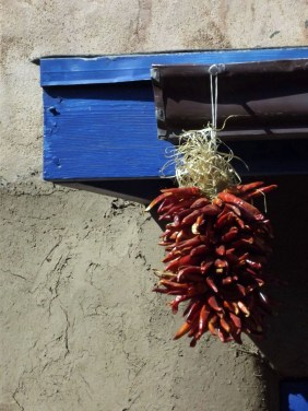 Chillies hanging from blue window frame