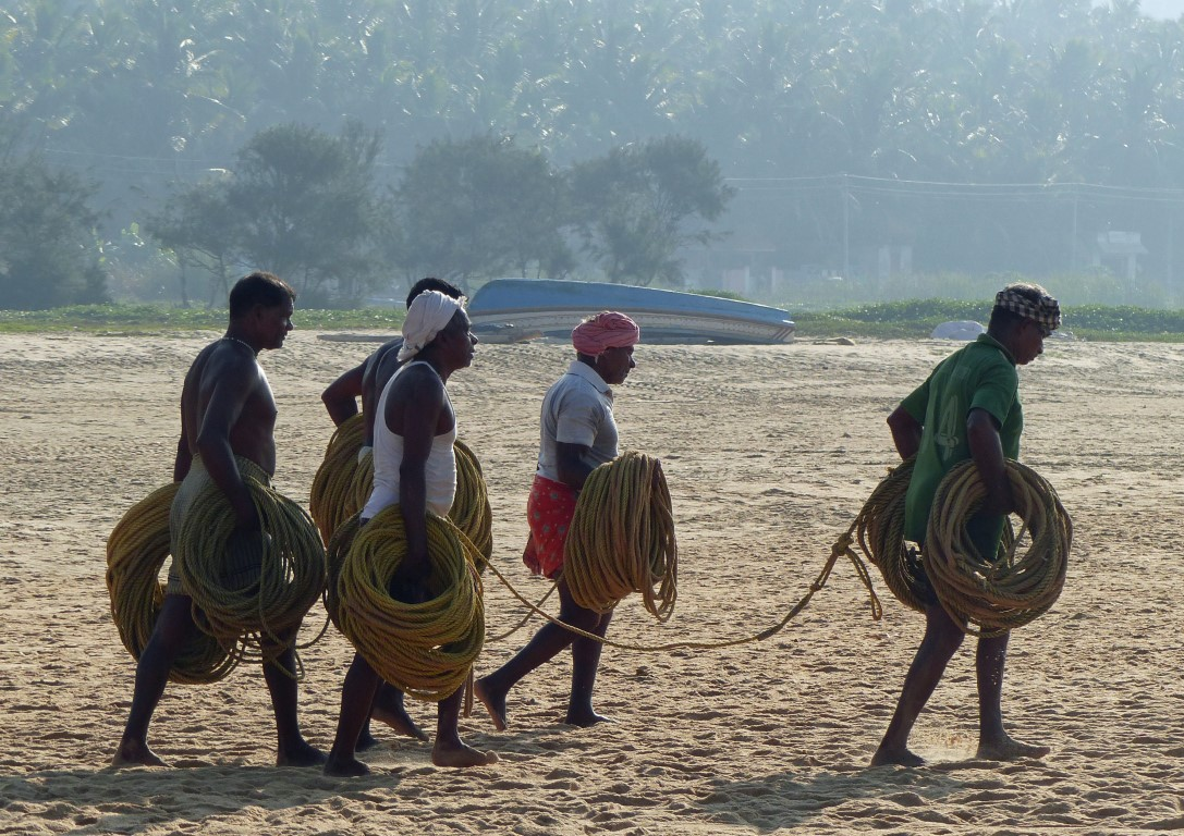 Men carrying lots of rope by the sea