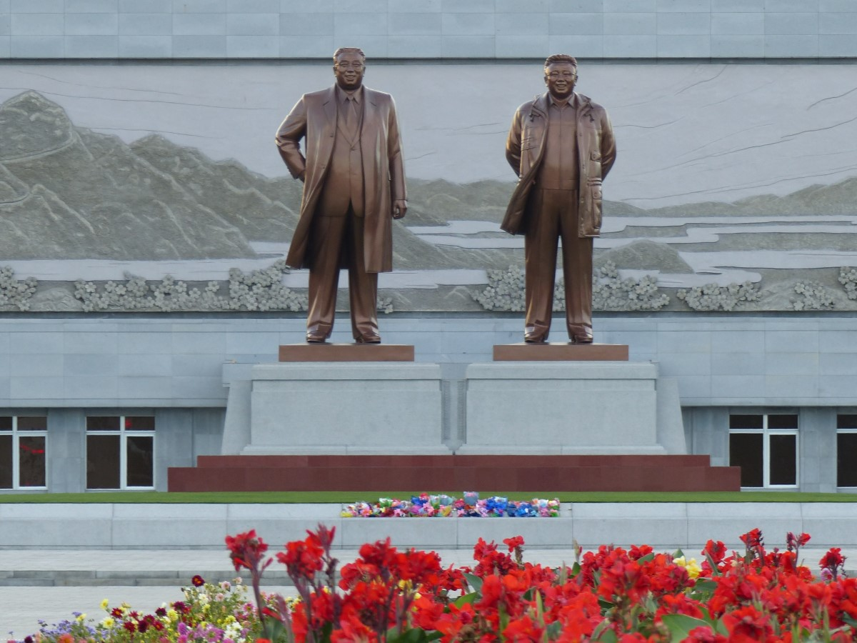 Large statues of North Korean Leaders with flowers in front