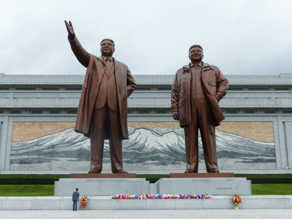 Large statues of North Korean Leaders and man laying flowers