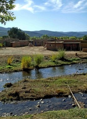 Small stream with pueblo houses on far side