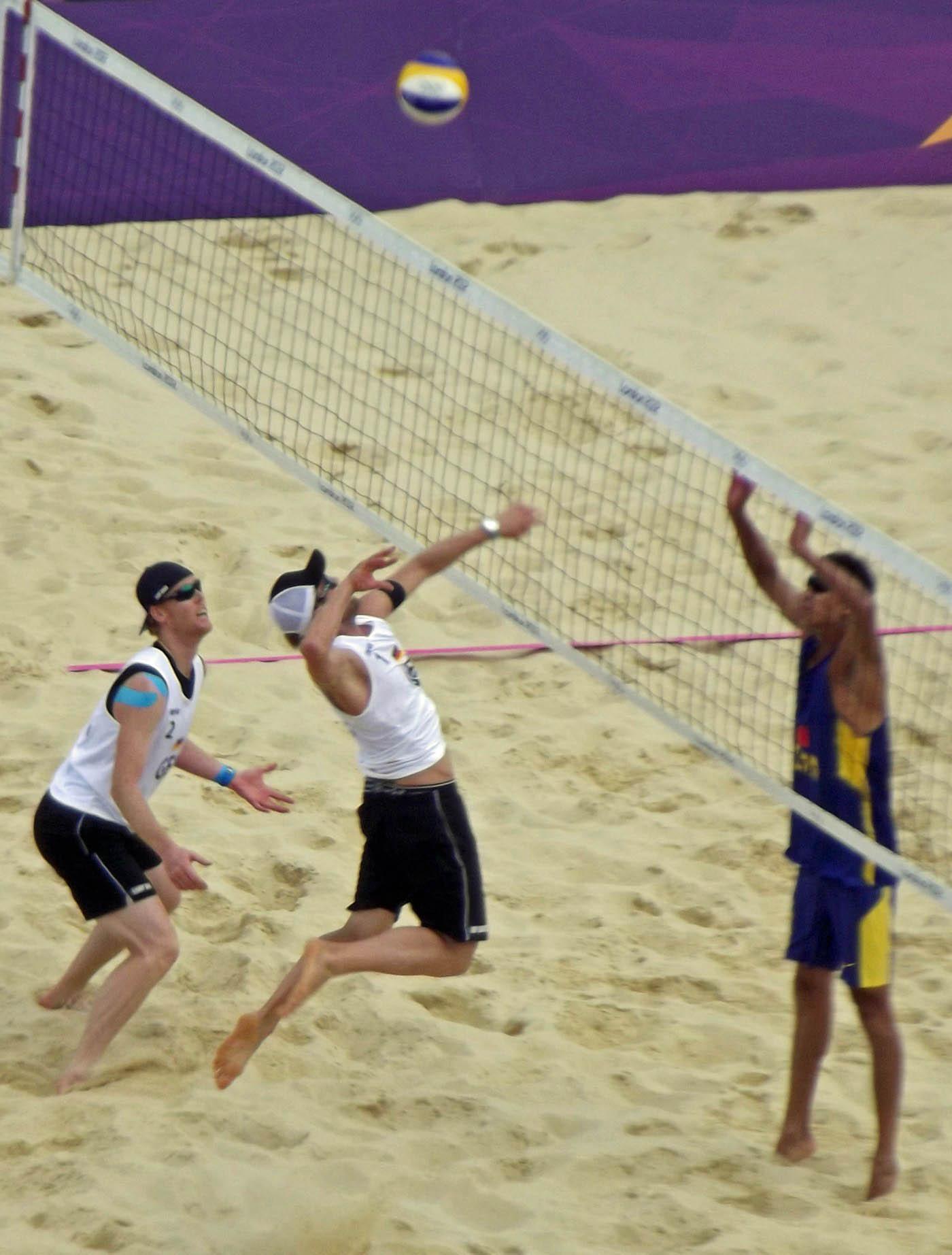 Three men playing beach volleyball
