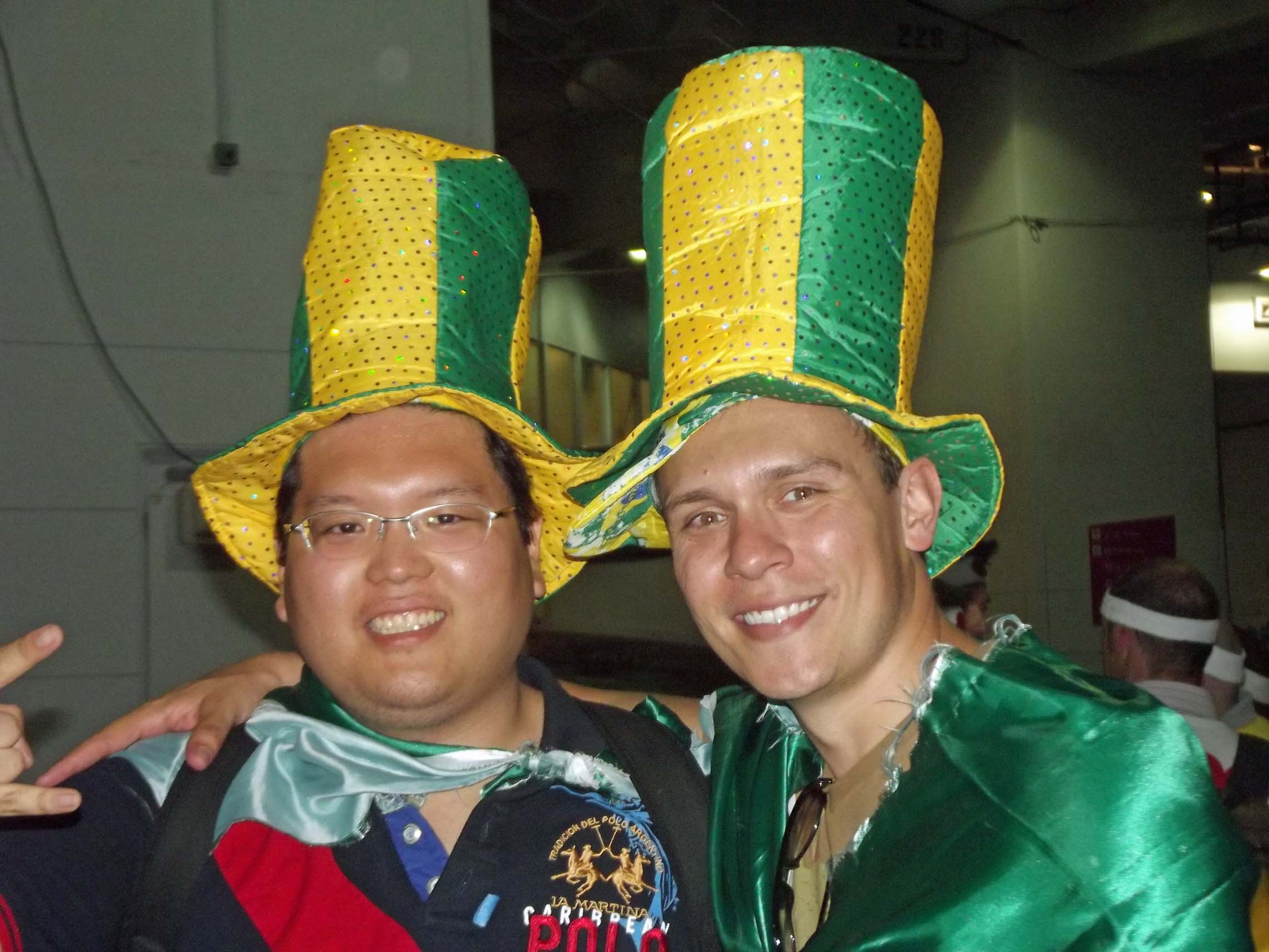 Two men in yellow and green hats