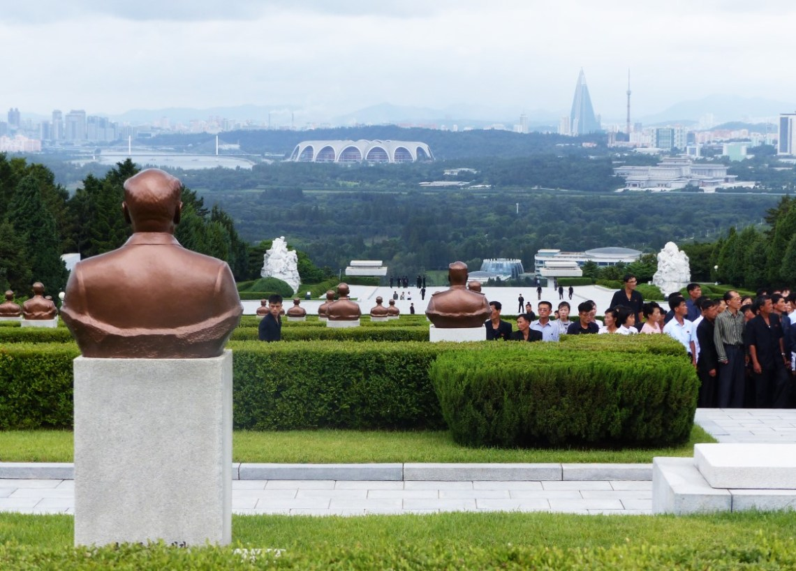 Memorials separated with low green hedges and city view beyond