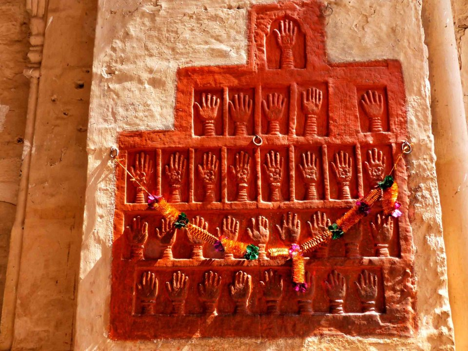 Terracotta coloured handprints on a wall