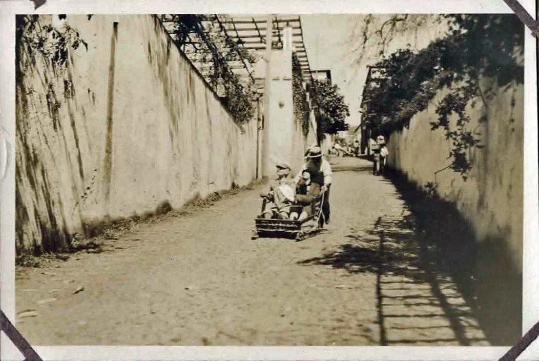 Old photo of people on a toboggan in cobbled street