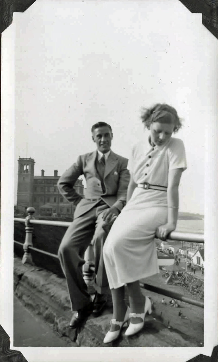 Old photo of a couple sitting on a railing by the sea