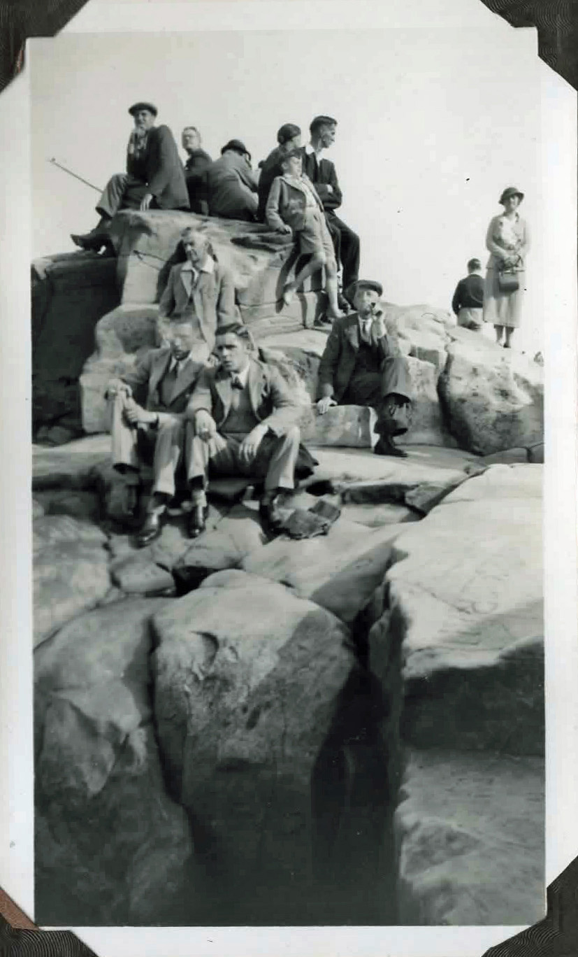 Old photo of a group of people sitting on rocks by the sea
