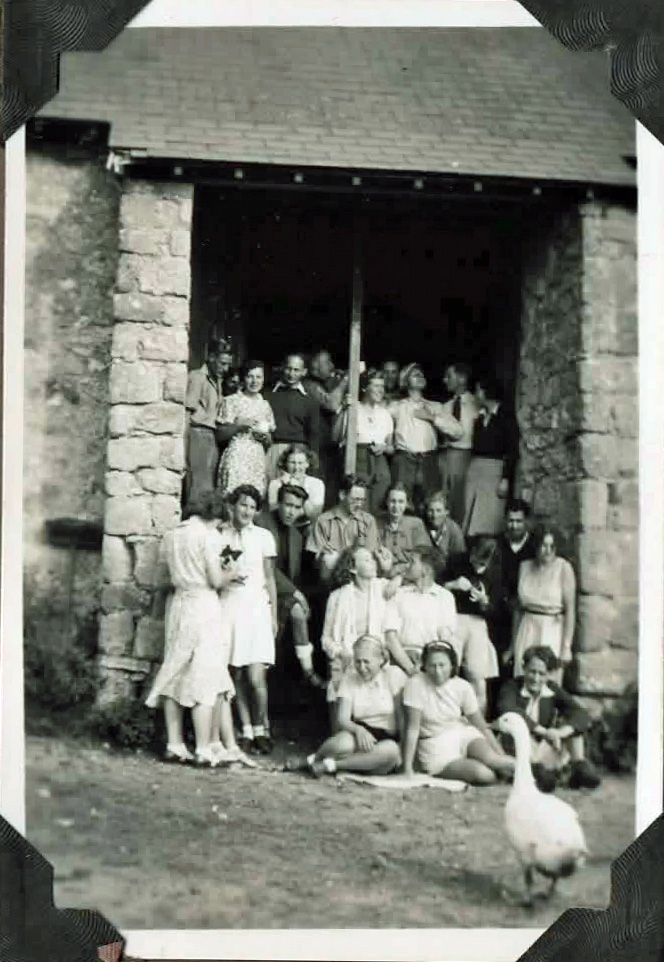 Old photo of group of people outside a barn