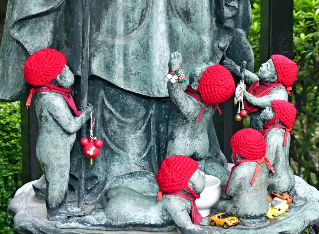Stone figures of babies wearing red caps and bibs
