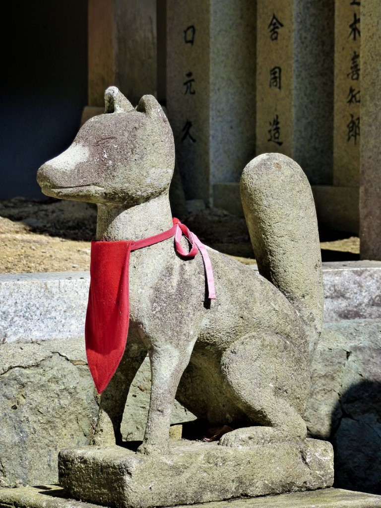 Stone fox wearing a red bib