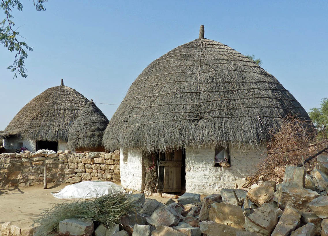 Several white-washed round huts