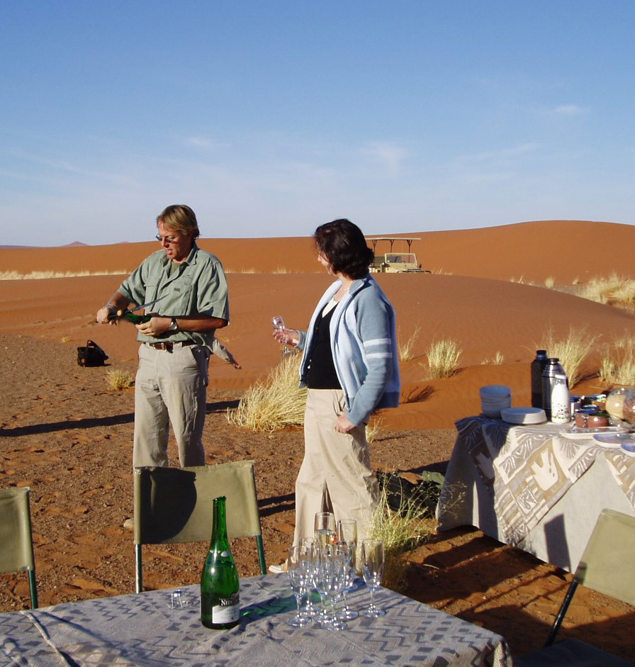 Two people opening champagne by a table in the dunes