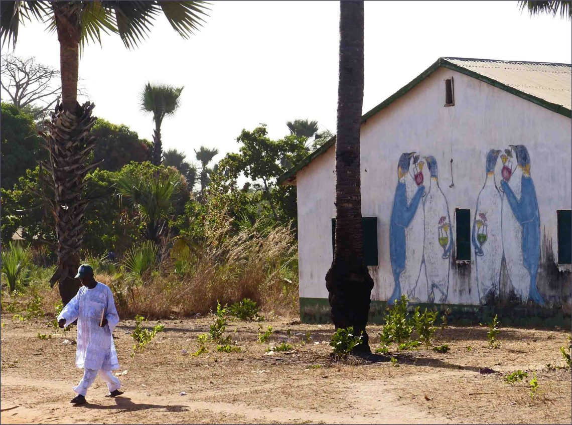 Man in white African dress walking past painted building