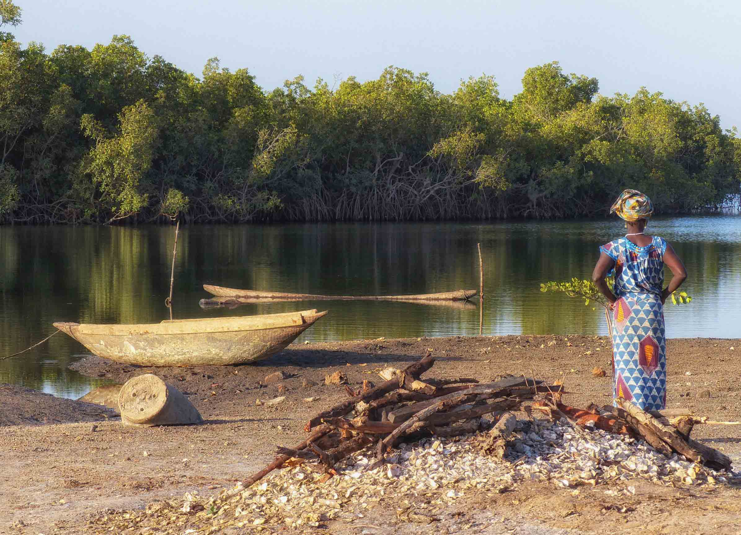 Woman standing by oyster shell pile, looking out at a river