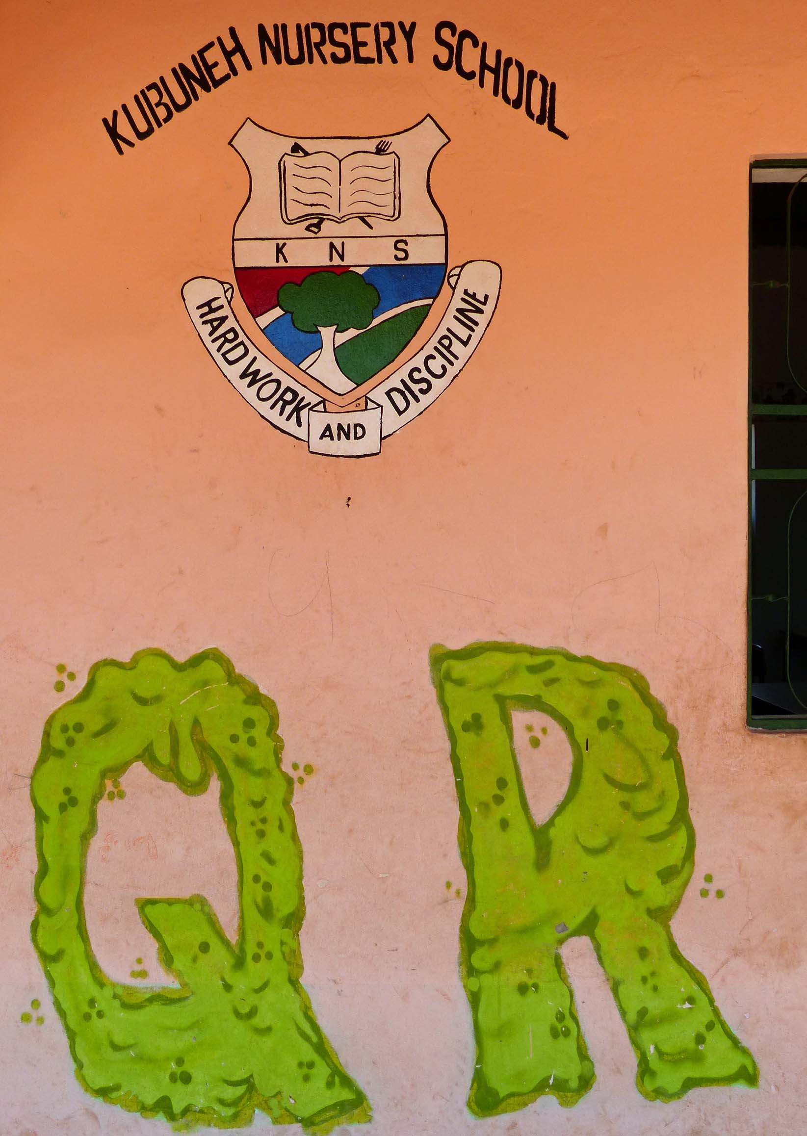 Crest and lettering on an ochre wall