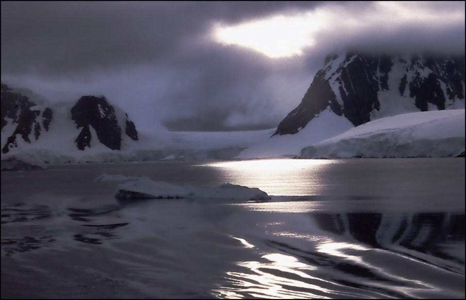 Calm silvery sea and snowy cliffs