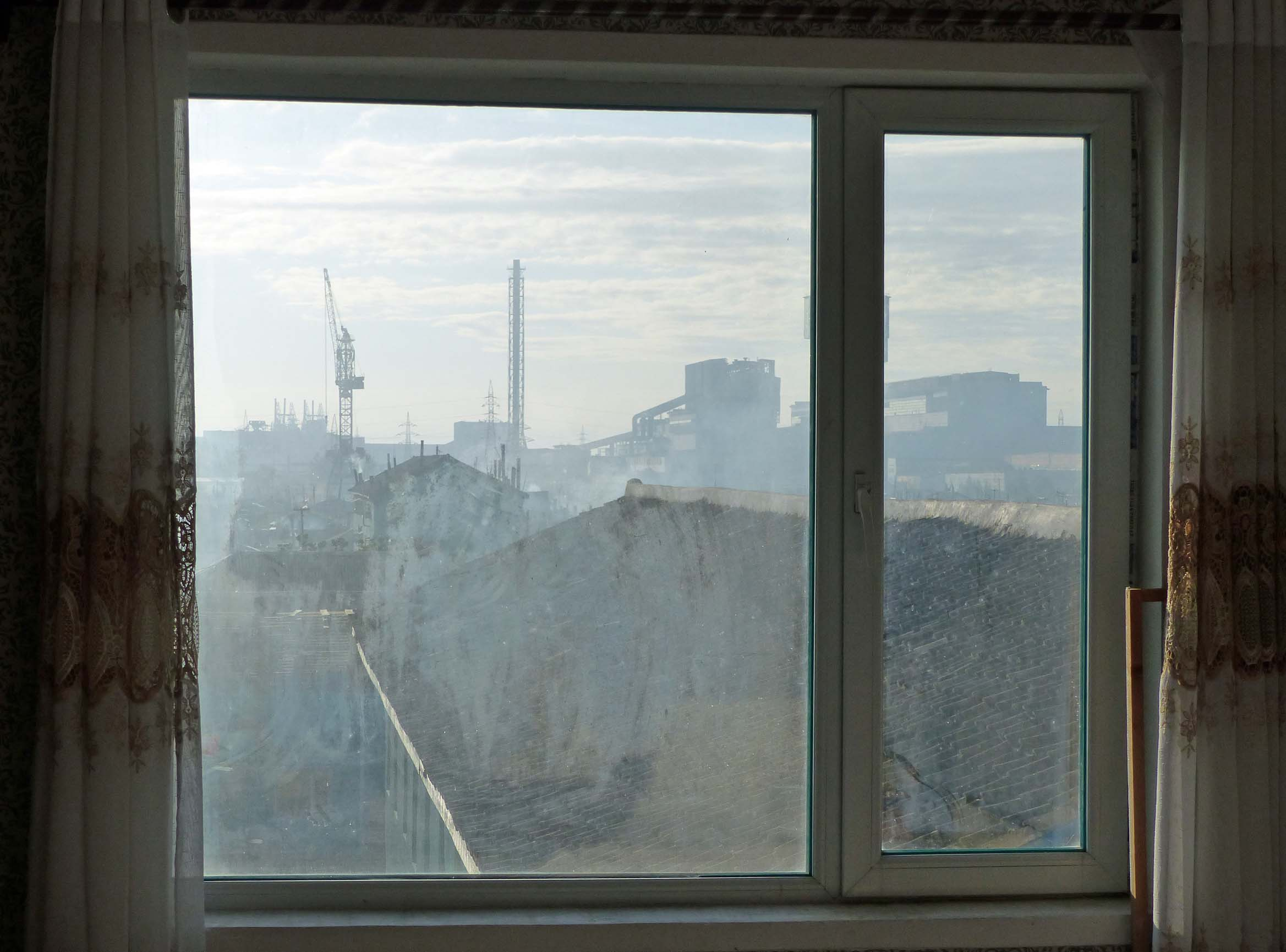 Dirty window and industrial skyline