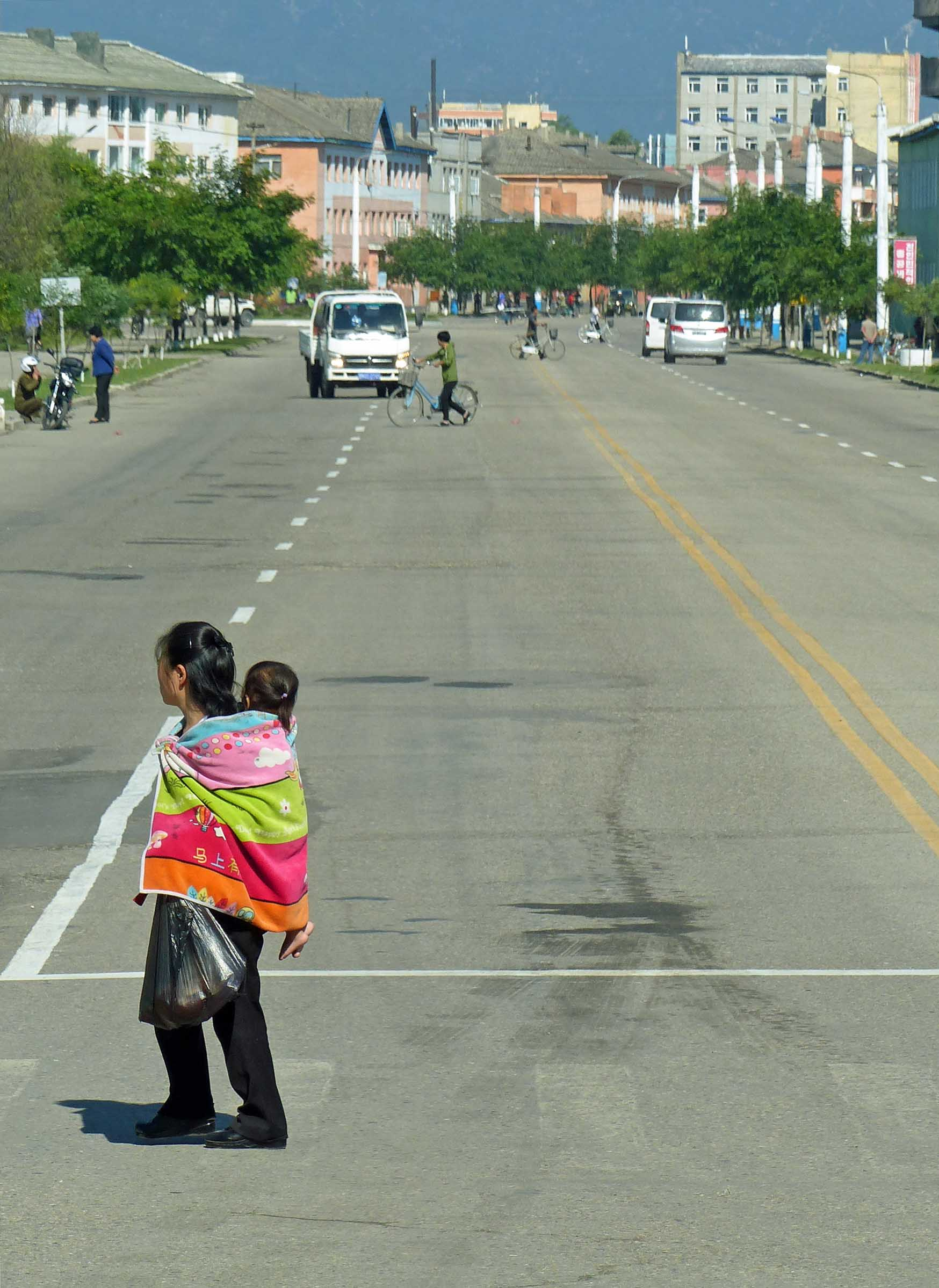 Lady crossing a road with child on her back