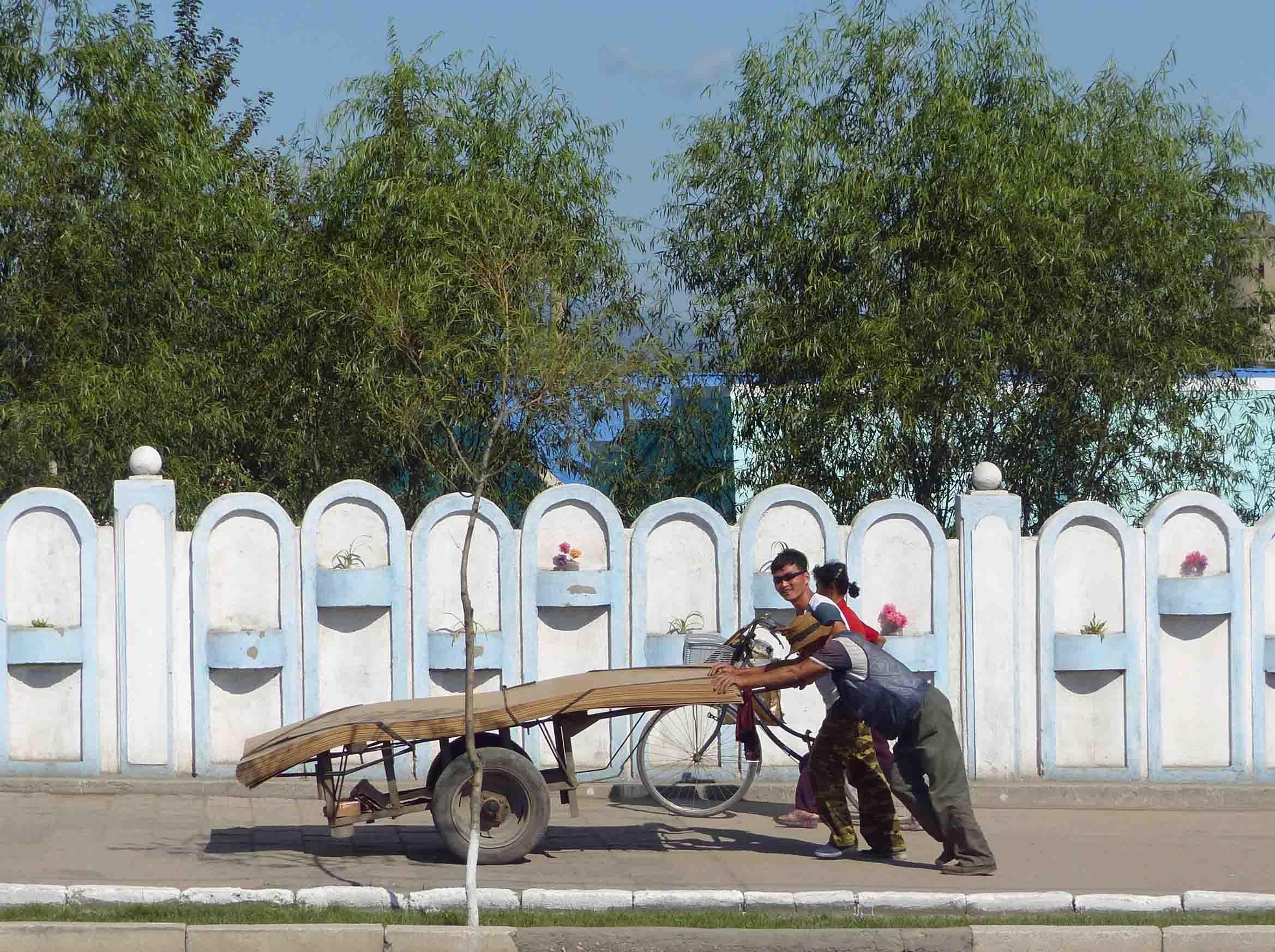 Men pushing cart with large piece of wood