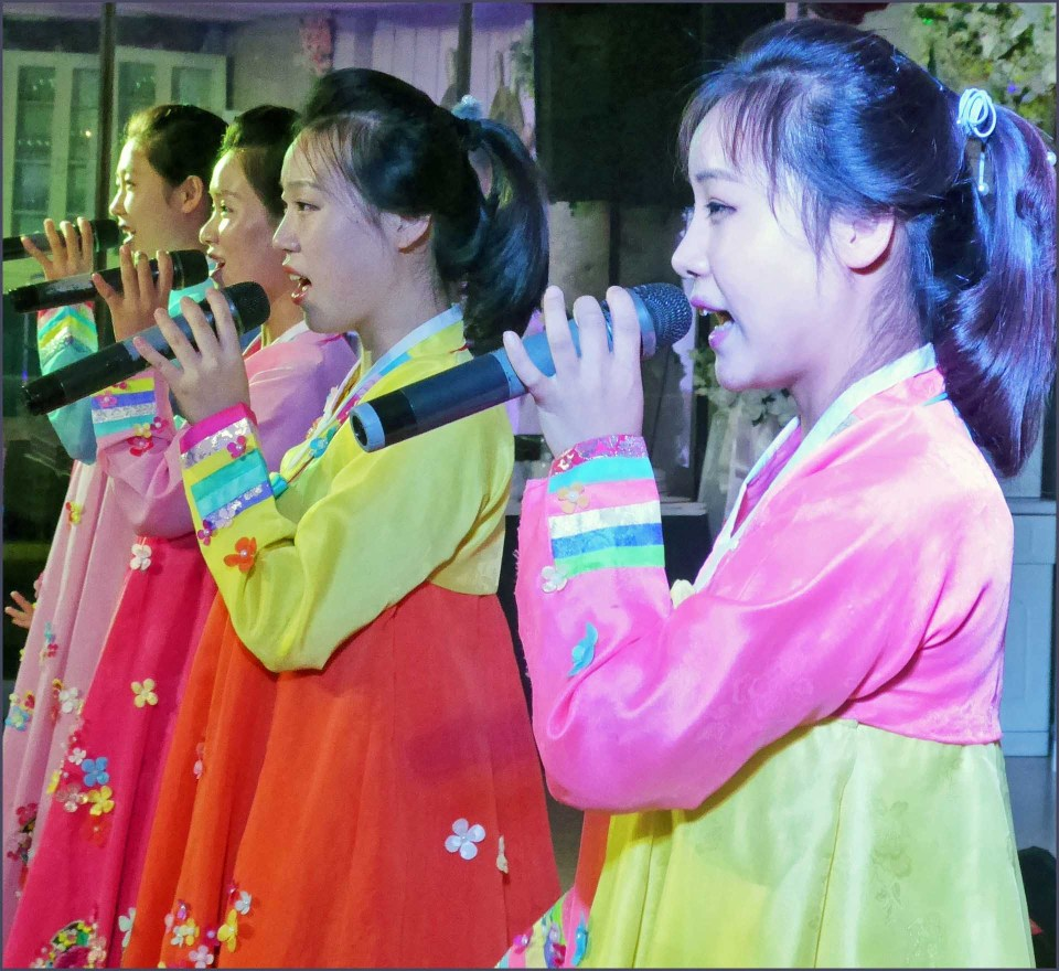Women in bright dresses with microphones