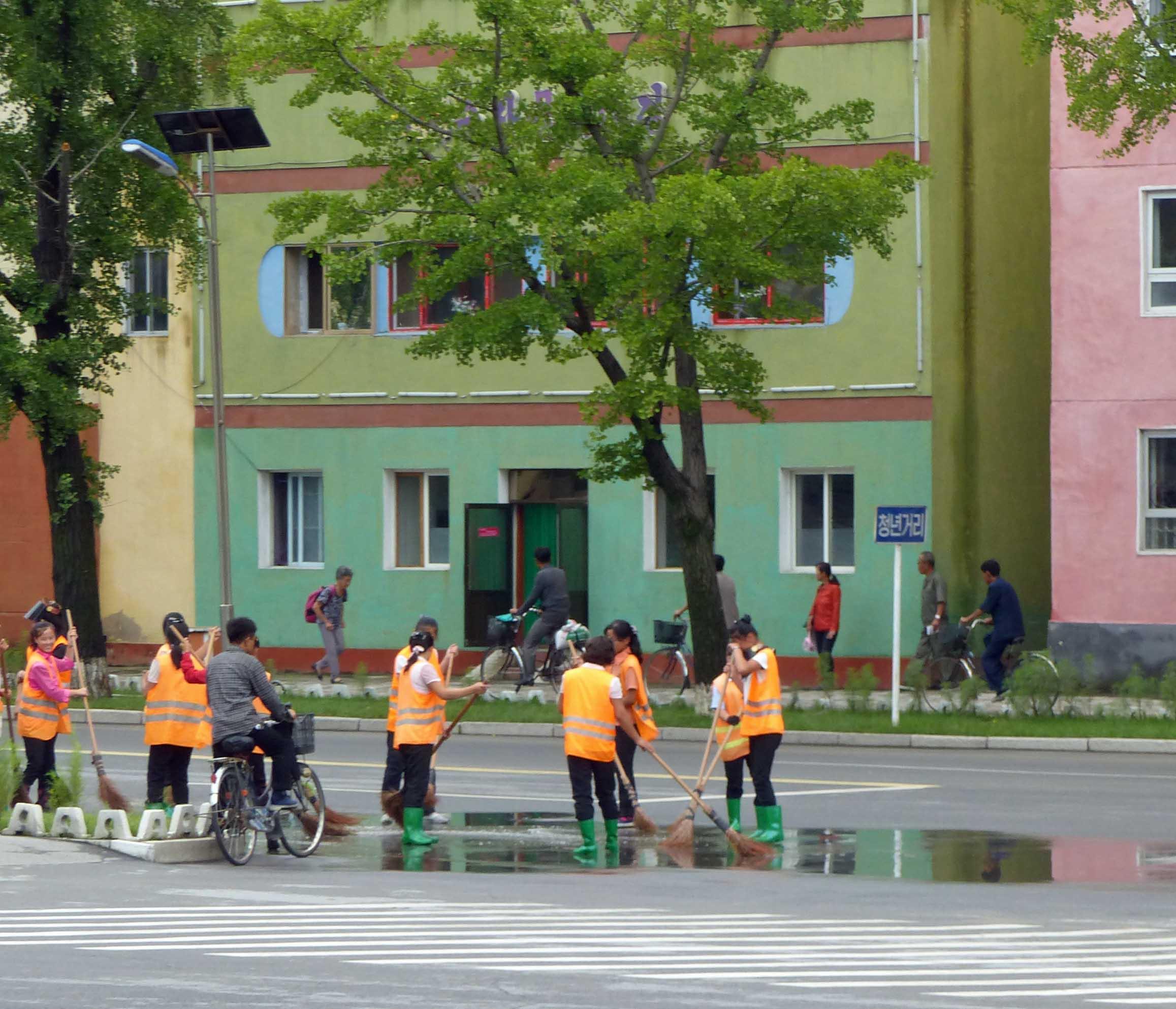 Women in orange sweeping street