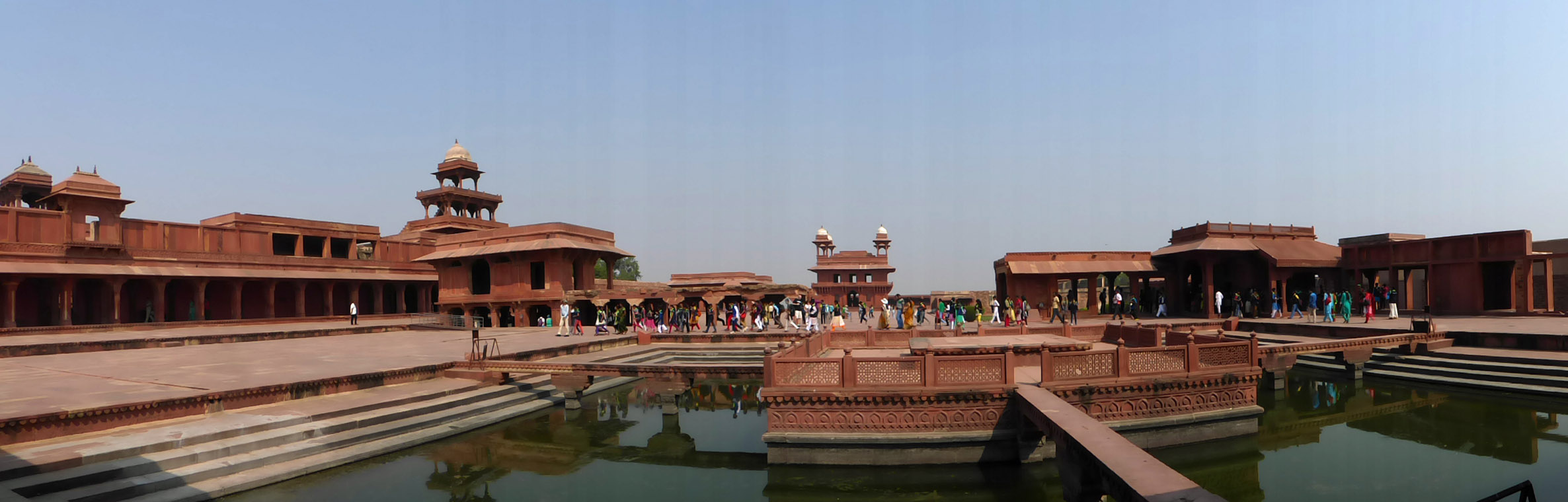 Red sandstone palace buildings and pool