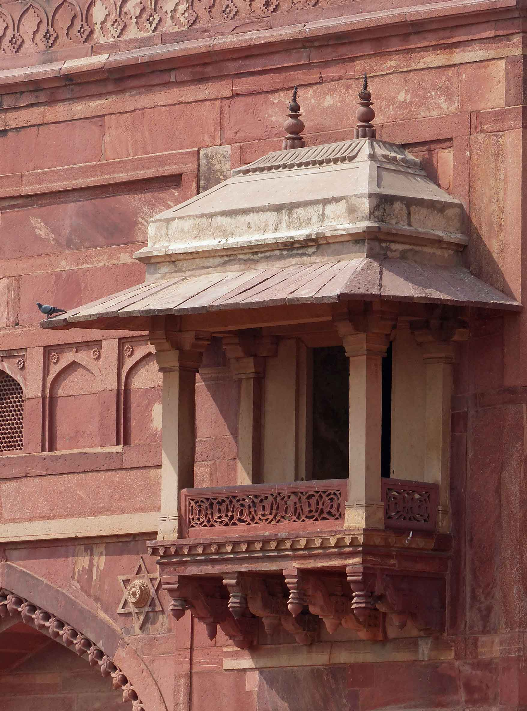 Red sandstone building with ornate balcony