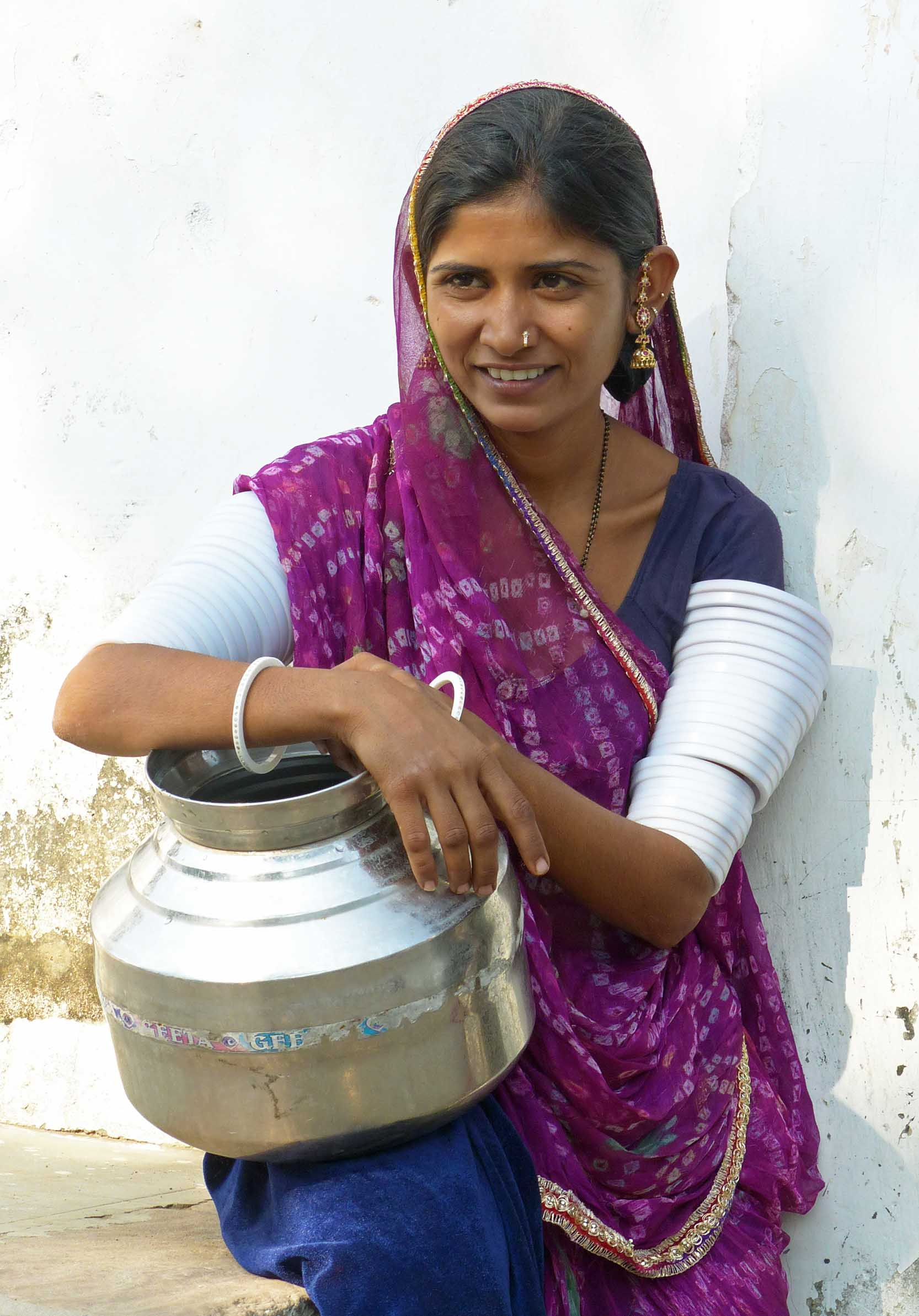 Young woman in blue and purple with metal container