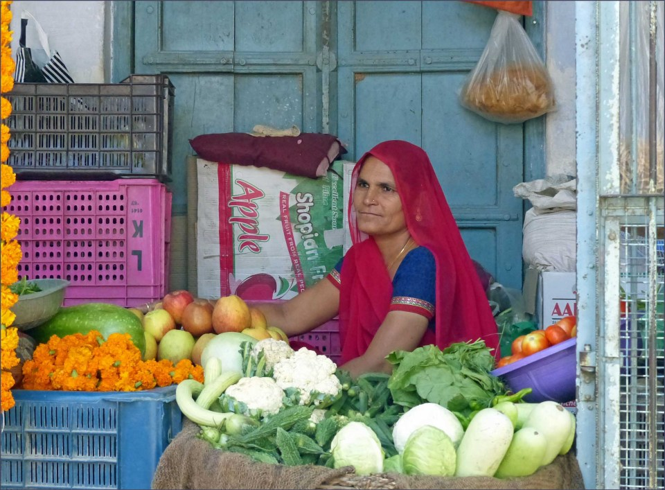Lady in blue and red surrounded by vegetables