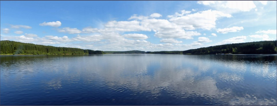 Panoramic shot of a lake with blue sky