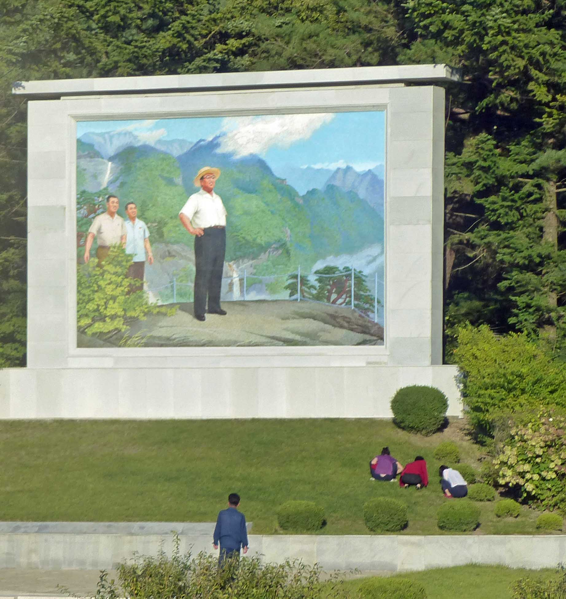 Women gardening in front of mosaic mural of Kim Il Sung