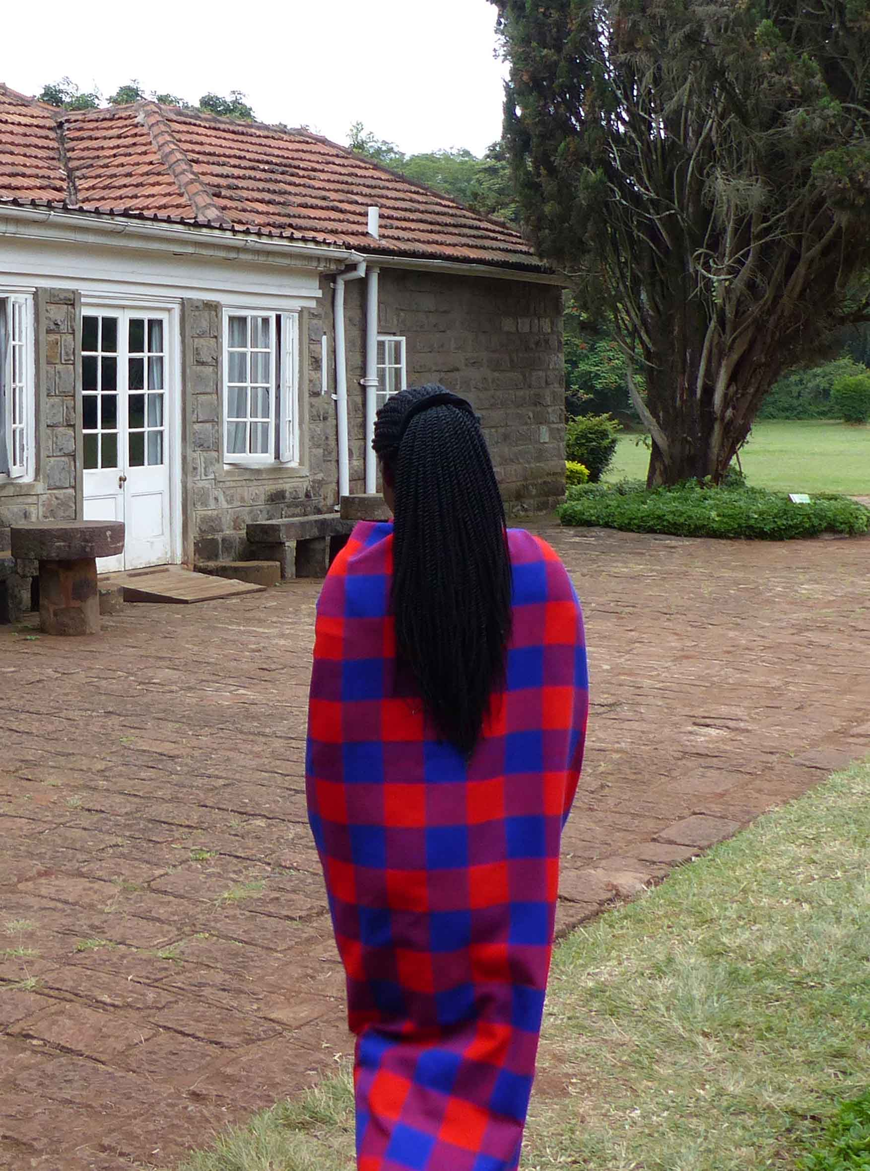 Young lady in blue and red checked blanket, from behind