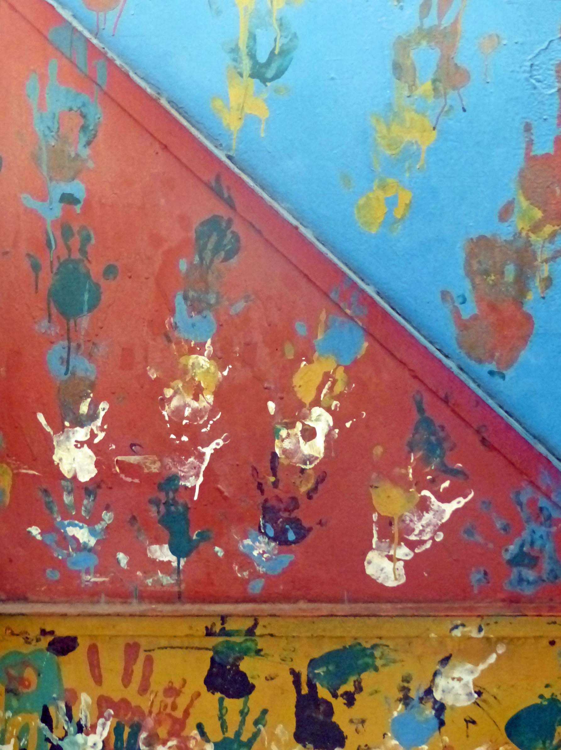 Paint handprints on a colourful wall