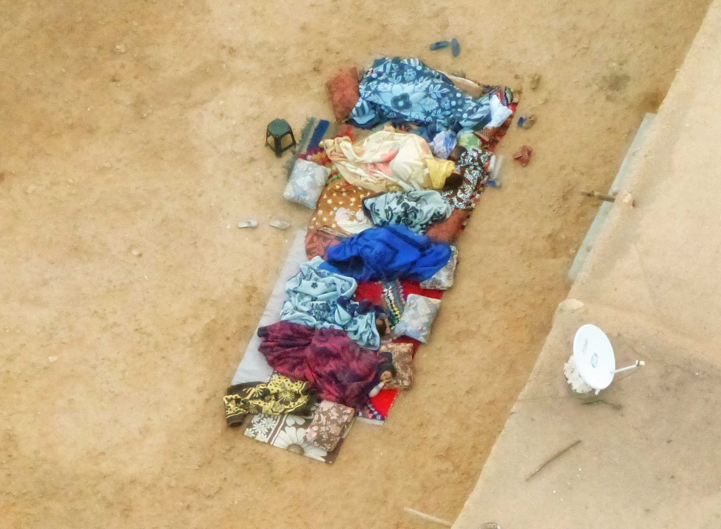 Aerial view of people sleeping under colourful fabrics