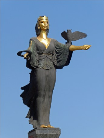 Statue of gold woman dressed in black