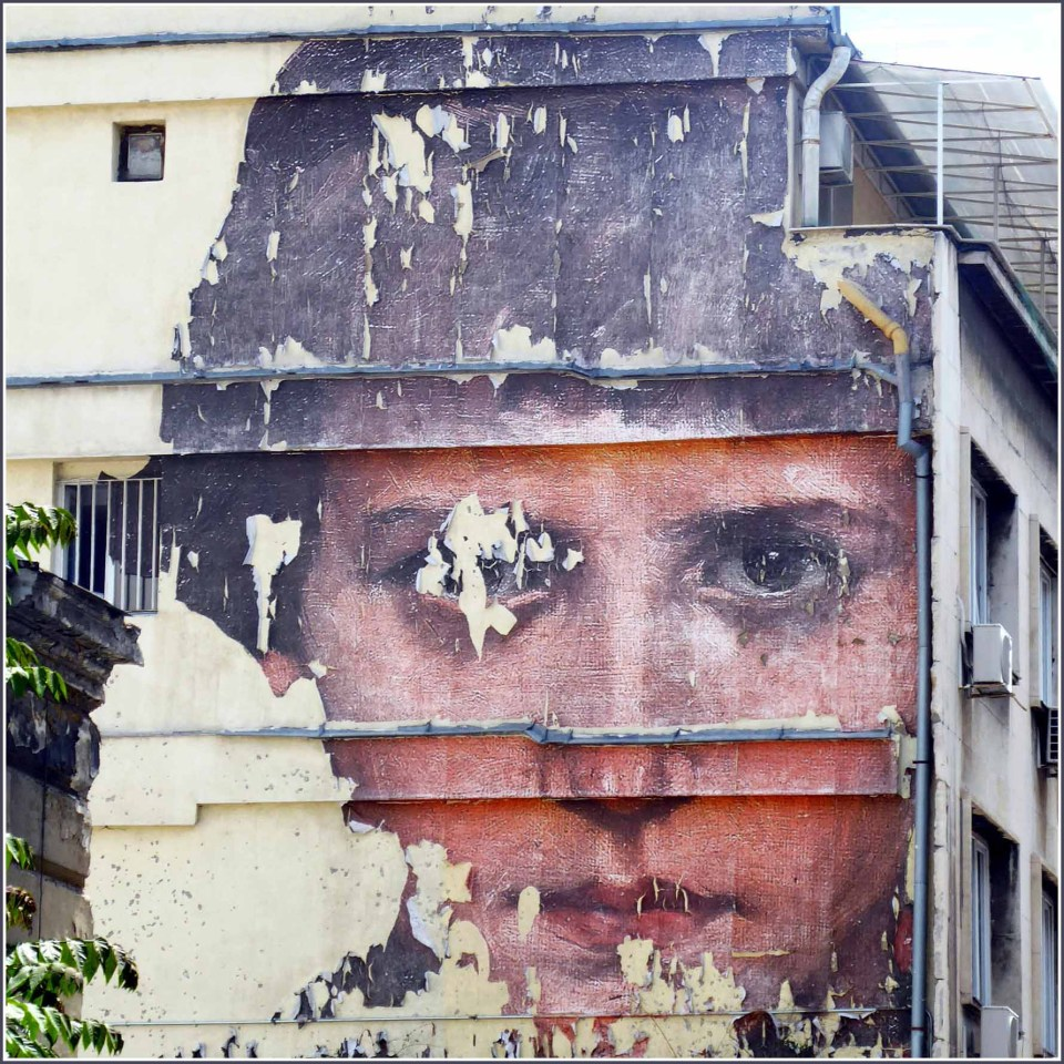 Peeling mural of a person's face