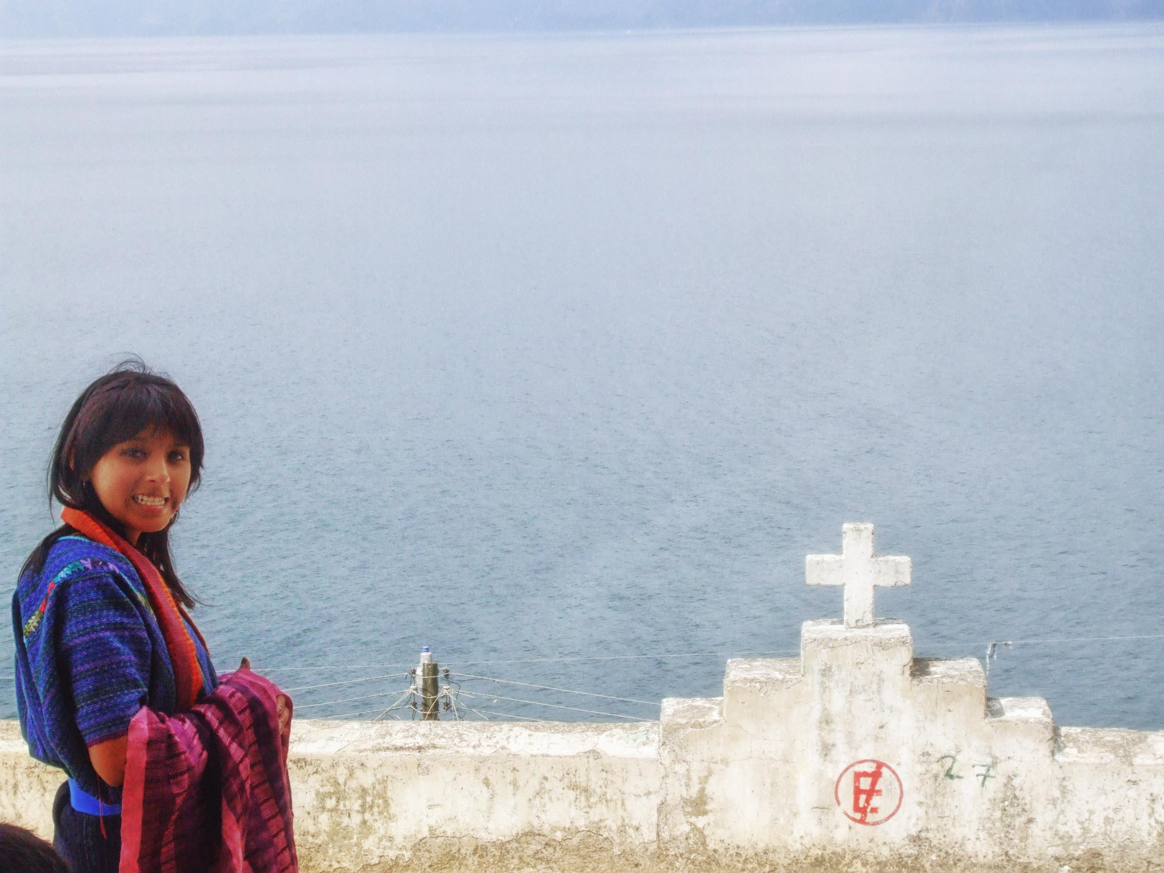 Girl in traditional blue clothing by stone wall with view of a lake
