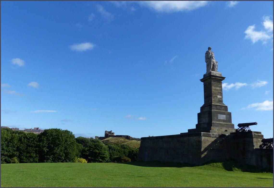 Stone statue on a plinth on a grassy hillside