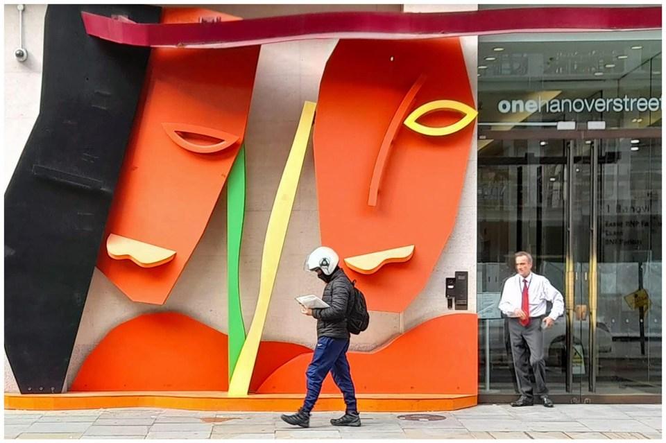 Man in helmet passing art installation