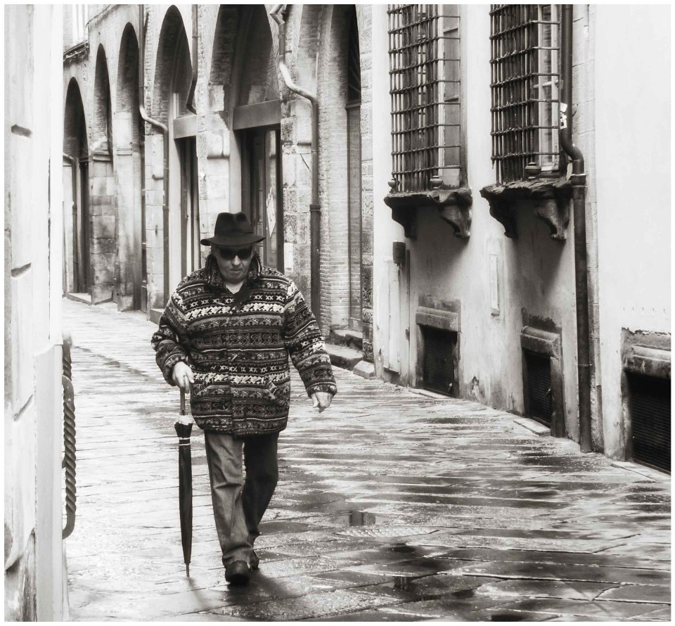 Man with umbrella, hat and sunglasses on a narrow street