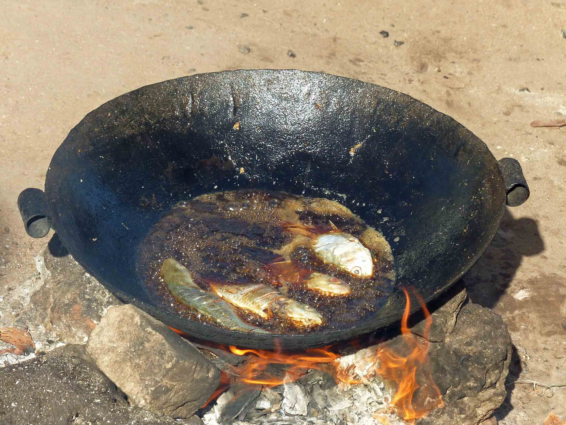 Four small fish frying in a pan