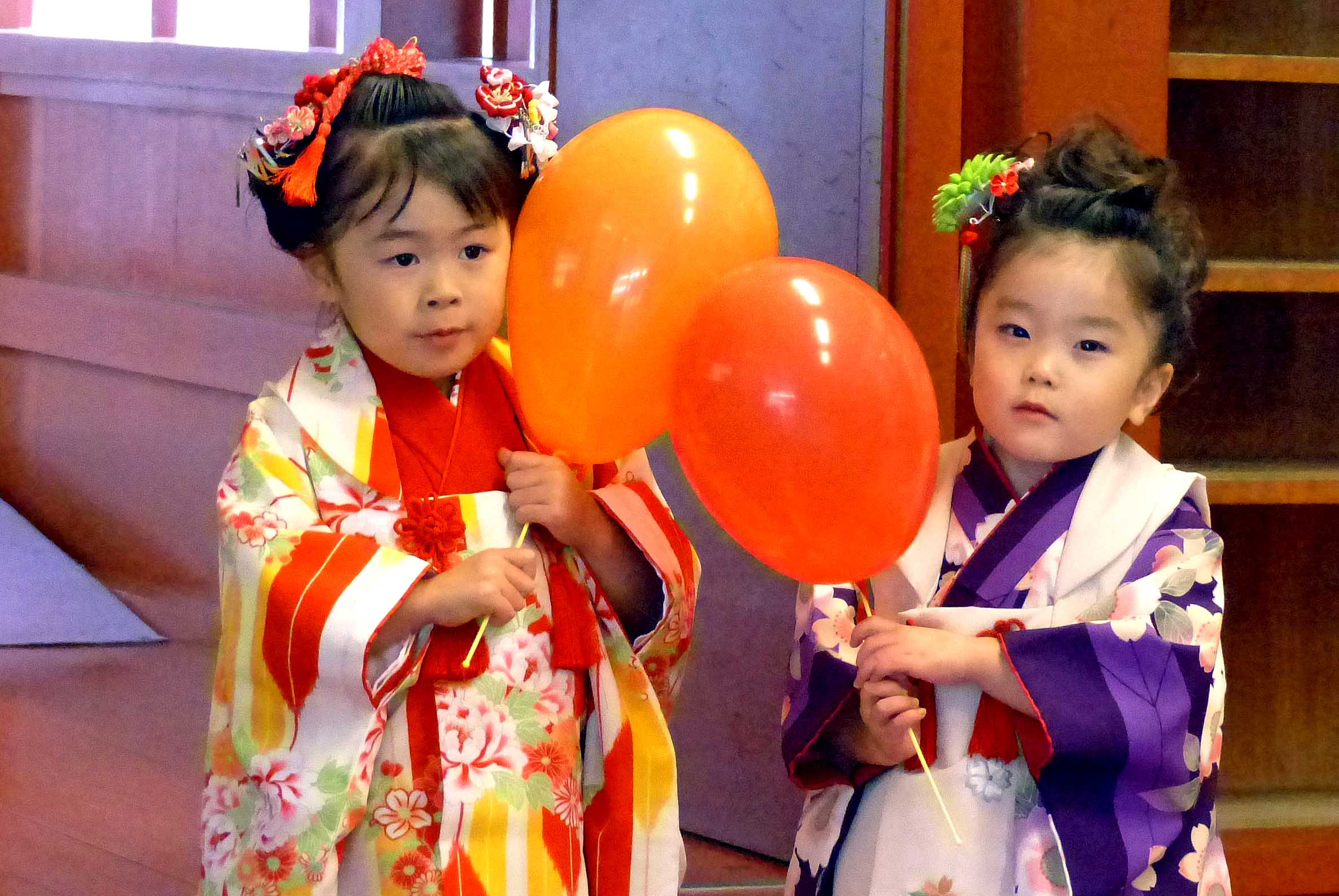 Two little girls in Japanese costume with balloons