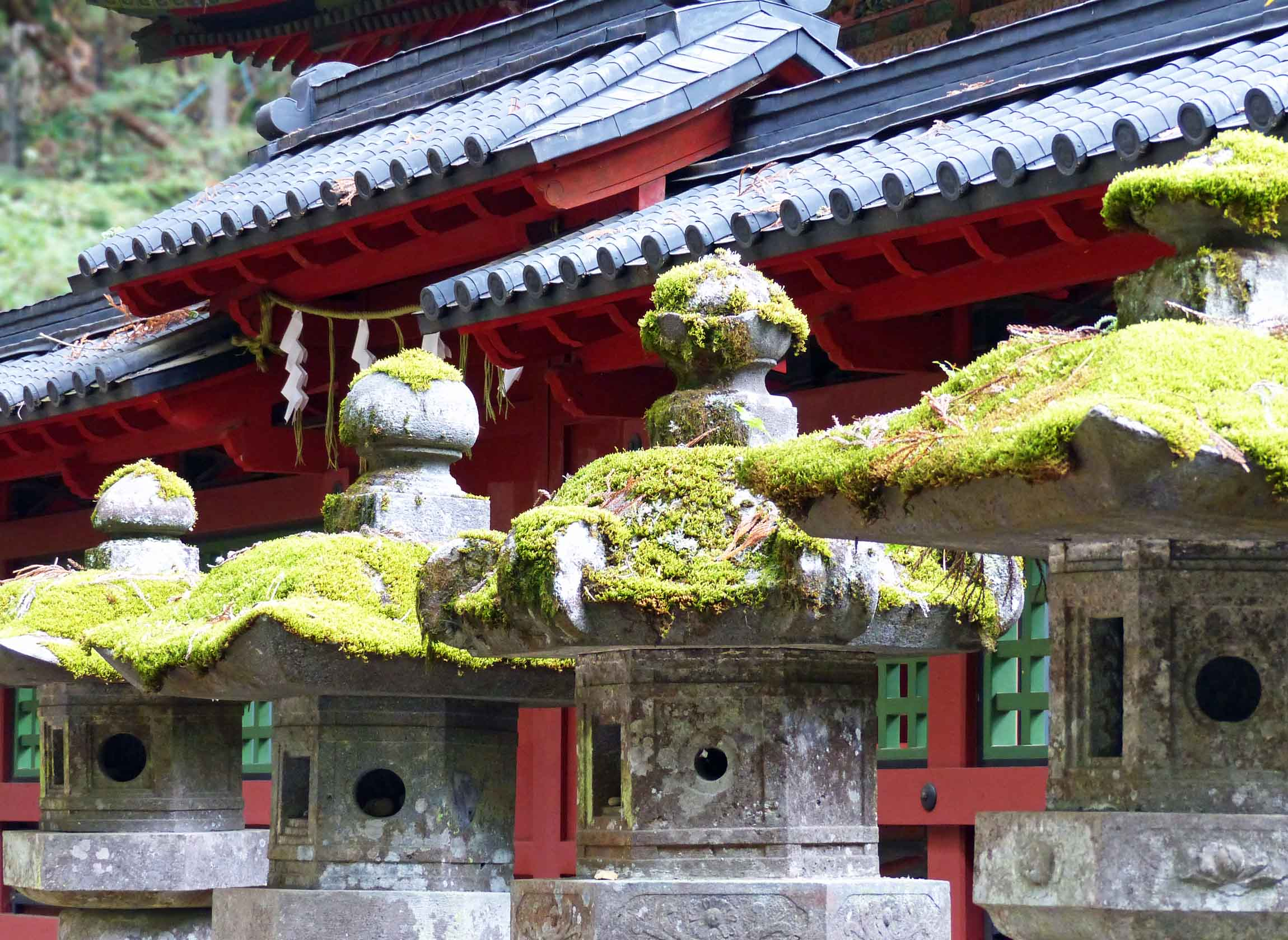 Buddhist temple with moss-covered stone lanterns