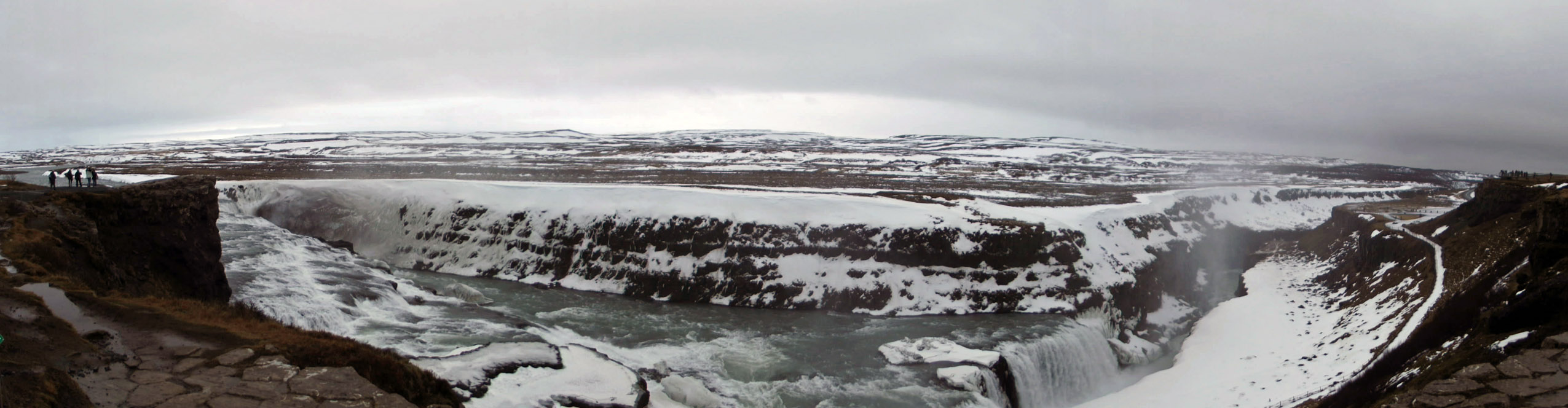 Panorama of large waterfall in snowy landscape
