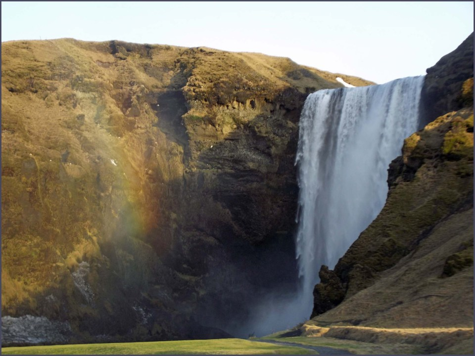 Tall waterfall with rainbow in spray