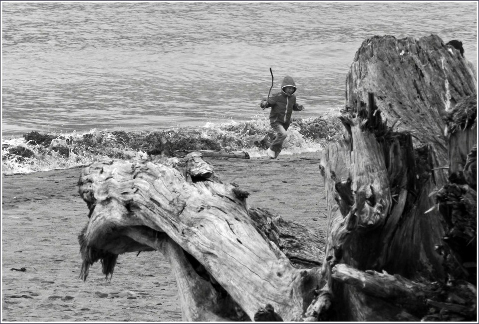 Black and white photo of child running by the sea
