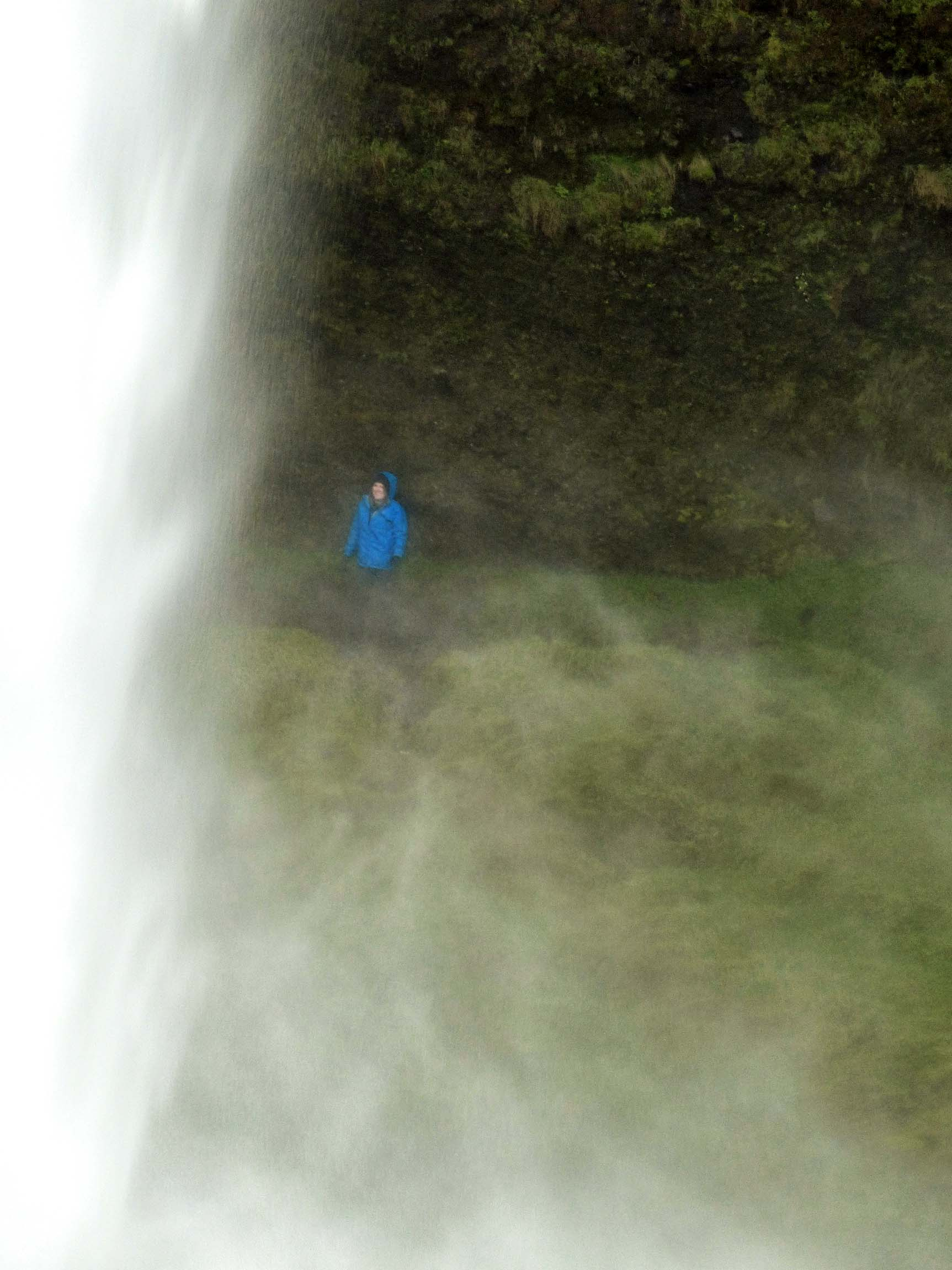 Person in blue jacket behind waterfall